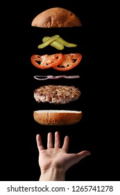 fly burger with beef sliced tomatoes pickles and onion on black. floating food levitating burger