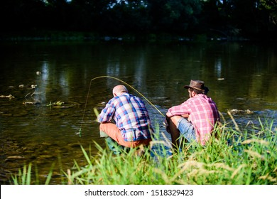 fly fish hobby of men. retirement fishery. happy fishermen friendship. Two male friends fishing together. big game fishing. relax on nature. retired father and mature bearded son. Fishing is fun.