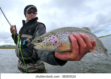 A fly fisher holds a beautiful rainbow trout in Alaska