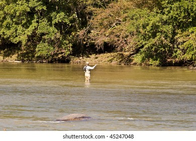 A fly fisherman casting his line in a muddy river