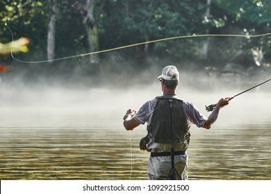 Fly Fisherman Casting Line While Wading In A Tennessee River