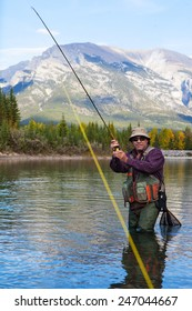 Fly fisherman Fighting a fish in a mountain river.