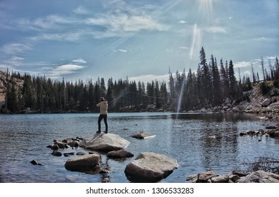 Fly Fisherman fishing a remote backcountry lake Standing on a rock in the lake. Casting a Fly Rod on a backcountry lake. Fishing mountain lake.