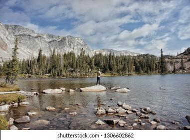Fly Fisherman fishing remote backcountry high alpine lake. Fishing in Wyoming, Colorado, Montana and Idaho