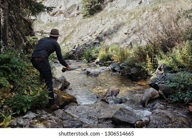 Fly Fisherman fishing a small Creek in the Mountains.
