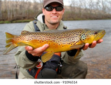 Fly fisherman holding a huge Brown Trout fish prior to releasing into the river