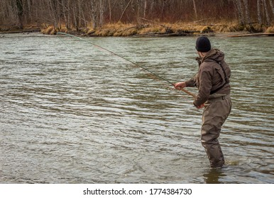 A fly fisherman hooked into a big fish in a the Kalum River, British Columbia, Canada, with the rod bent