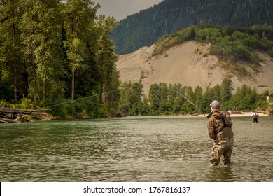 A fly fisherman hooked into a fish on a river with mountains and trees in the background on the Kitimat River, British Columbia.
