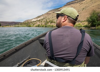Fly fisherman sitting in a drift boat while floating the river to get to the next fishing access on the Lower Deschutes River near Warm Springs Oregon.
