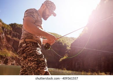 Fly fisherman using fly fishing rod on mountain lake.Replacing a lure and streamers.