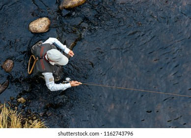 Fly fisherman using flyfishing rod in beautiful river