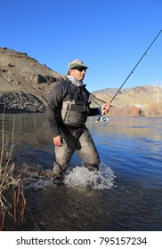 fly fisherman wading in big river