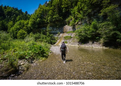 Fly Fisherman wading through shallow water in a wide gorge in Switzerland in search for trout in this wide clear river running along steep stone walls