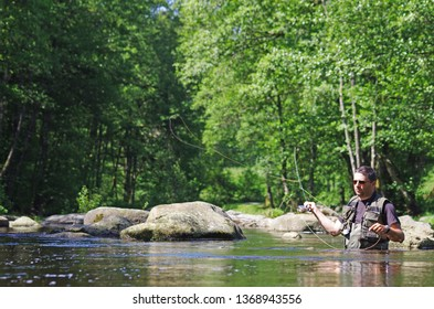 Fly fishermen in action. Catch of fish, fly fishing scene, freshwater fishing, trout fishing