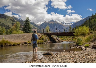 Fly fishing Angler wading & casting a fly rod  on the beautiful San Miguel river outside of Telluride, Colorado.