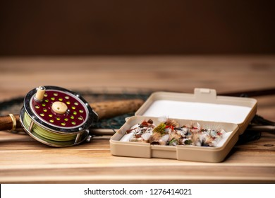 Fly fishing equipment: flies, a net, a rod and a reel gathered together on a wooden table.