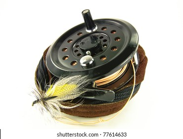 Fly Fishing Reel:  A well-used fishing reel sits atop its leather case along with a lure made for fly-fishing.
