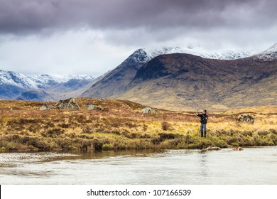 Fly fishing in a river with snow covered mountains in the back