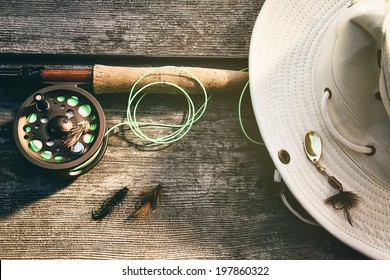 Fly fishing rod with canvas hat on wood