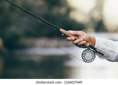 Fly fishing rod in fisherman hand.