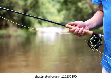 fly fishing rod in hand.