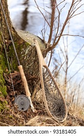 Fly fishing rod and net at a tree