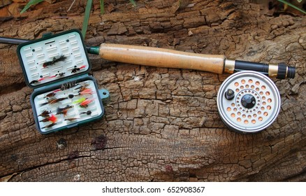 Fly fishing rod reel and artificial flies on a log outdoors