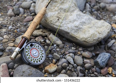 A fly fishing rod and reel on the river bank.  Fishing scene on the banks of the Soda Butte Creek in Yellowstone National Park.