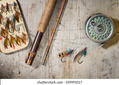 Fly fishing rod, reel and vintage salmon flies in box on a distressed white wooden background