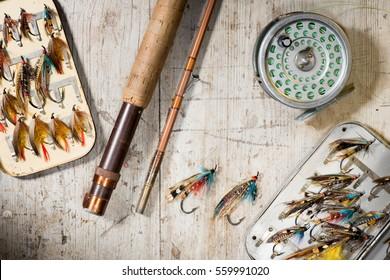 Fliegenfischer, Rollen und Vintage-Lachs fliegen in Kisten auf weißem Holzhintergrund