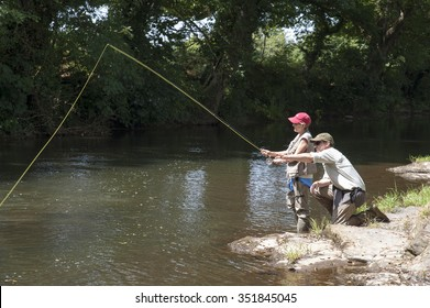 FLY FISHING A WOMAN WITH INSTRUCTOR ON AN ENGLISH RIVER UK - July 2013 - Fly fishing a gillie instructing a female pupil on the River Lyd in Devon England UK