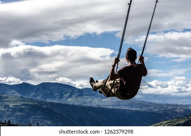 Fly. Man on swing kneeling in the mountains. Freedom