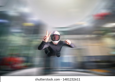 Fly men show v and peace. Indoor skydiving in wind tunnel. Men fly in white helmet and black suit. Numeral 2 and 5