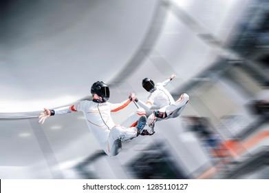 Fly Men. Skydiving team of flying people in wind tunnel . indoor skydiving