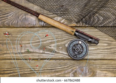 Fly rod , flies and landing net lying on an old wooden table. Line drawn I love fly fishing.