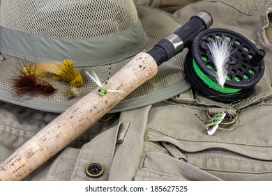 Fly Rod and reel with lures against fishing vest and hat.