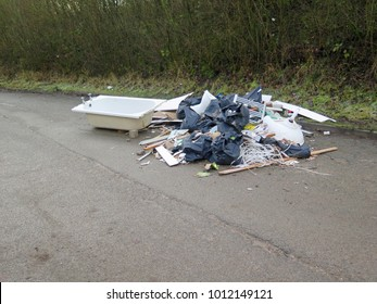 Fly tipped rubbish dumped in a country lane