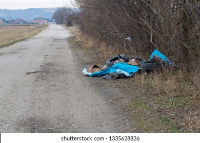 Fly tipped rubbish dumped in a lay-by in a country lane. Heap of illegally dumped household rubbish left on a side of the cart-road. Roadside fly tipping, dumping and polluting. Dumped rubbish.