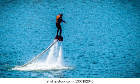 Flyboard. Air Farthest flight by hoverboard. Man flying on Board, Tallinn. Flyboard is aerial machine for personal watercraft, allows propulsion underwater. Copy space for design, text box. Blue lake