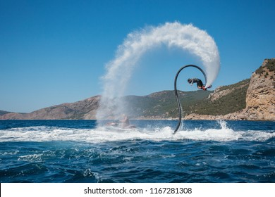 Flyboarding and seariding on the Sea near the mountain island. Water summer extreme sports.
