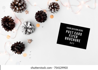 flyer mock up for branding for christms time, pine cones, tree branches and chirstmas decor on white background, flat lay top view.