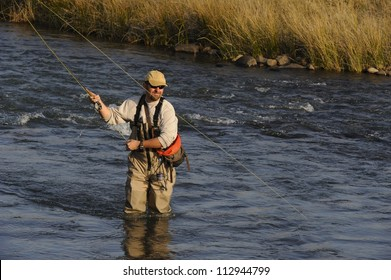 Fly-fisherman casting to trout on the Umzimkulu river,Underberg,Southern drakensberg, Kwazulu natal, South Africa.  The Umzimkulu lies at the heartland of South Africa's trout fishing region