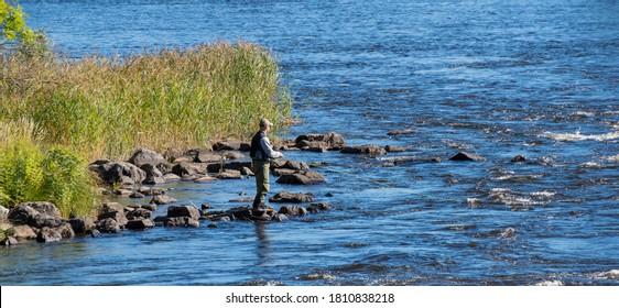 Flyfisherman using flyfishing rod in a river. Farnebofjarden national park in Sweden.