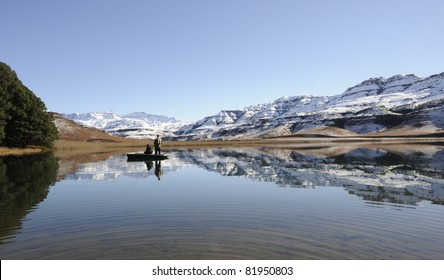 flyfishing for trout against a backdrop of snow at giants cup wilderness reserve, kwazulu natal, south africa