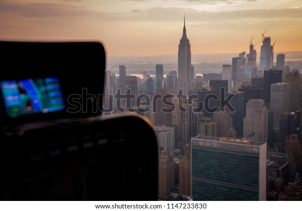 Flying above East River and Midtown in Manhattan, New York City on a helicopter. Beautiful NYC skyline at sunset.