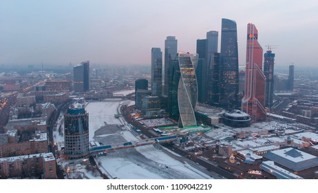 Flying above the snow-covered city and frozen river Moskva. Nice smooth shot of Moscow-city business towers with illuminated windows.