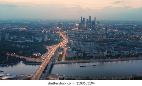 Flying above the wide illuminated city highways and Moskva river. Cityscape at dusk. Moscow-city towers in the evening haze on the horizon.