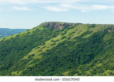 Flying aerial photo of high hillside rocky ridge landscape with trees bush vegetation in rural summer terrain.