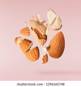Flying in air fresh raw whole and cut almonds  isolated on pink background. Concept of Almonds is torn to pieces close-up. High resolution image