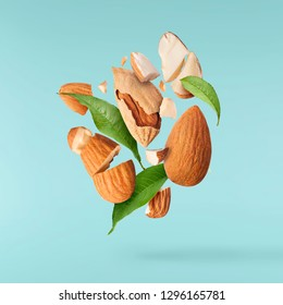Flying in air fresh raw whole and cut almonds  isolated on turquoise background. Concept of Almonds is torn to pieces close-up. High resolution image